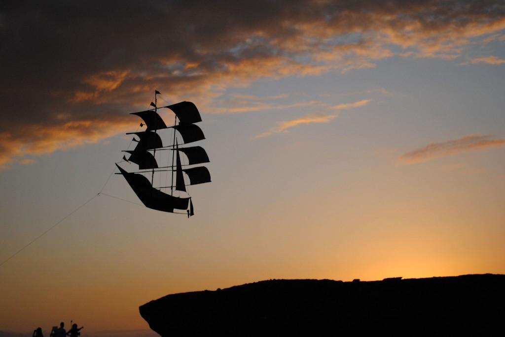 Un aquilone solca le nubi verso il tramonto, Bali